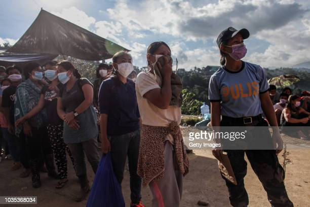 Families wait to claim the bodies of their loved ones who were killed by a landslide on September 18 2018 in in Itogon Benguet province Philippines...