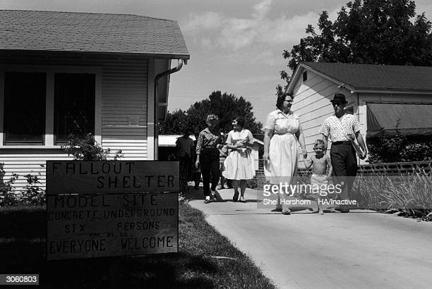 Families walk down the driveway while touring a model site home with a concrete basement fallout shelter Texas 1961