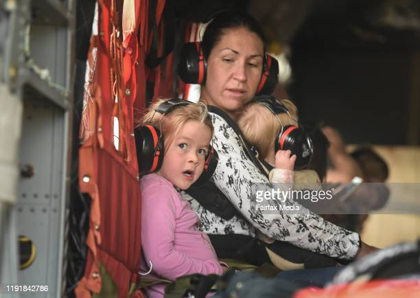 Families with small children and babies are evacuated by air from Mallacoota Airport on January 5 2020 in Mallacoota Australia Many parents with...