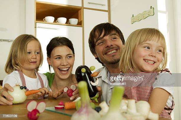 Familiy in kitchen, playing with children