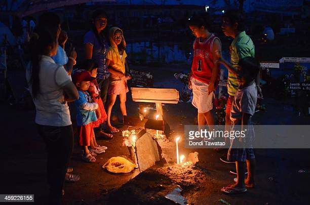 TACLOBAN LEYTE PHILIPPINES DECEMBER 24 A familiy visits the grave of a loved one who perished during typhoon Haiyan at a flooded mass grave on...