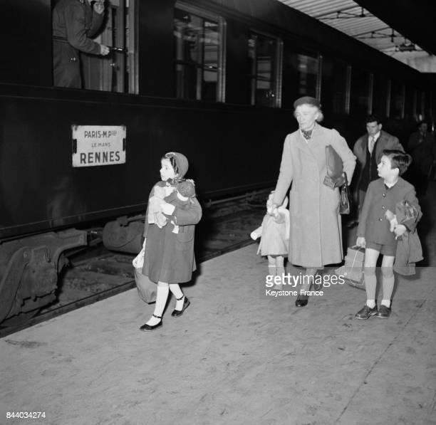 Famille prenant le train à la Gare Montparnasse pour les vacances à Paris France le 29 mars 1956