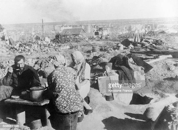 Famille russe qui a rejoint la ville et prend son premier repas sur les ruines de sa maison à Stalingrad Russie circa 1940