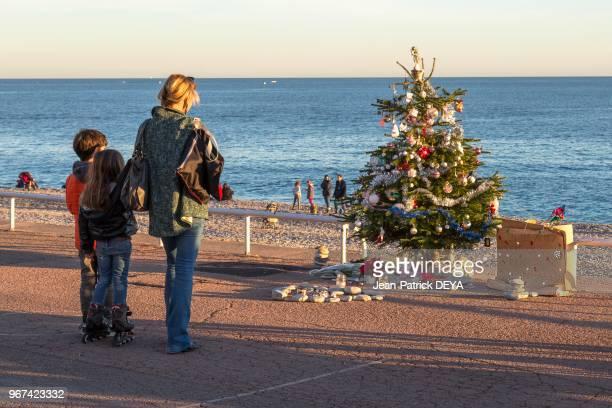 Famille se recueillant devant un arbre de Noel sur la Promenade des Anglais 28 décembre 2016 en hommage à un enfant victime de l'attentat du 14...