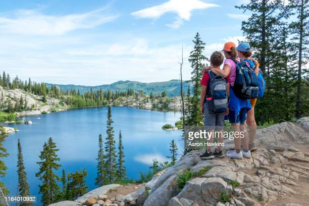 family admiring a panoramic scene above a mountain lake - lake mary in the wasatch mountains of utah - utah stock pictures, royalty-free photos & images