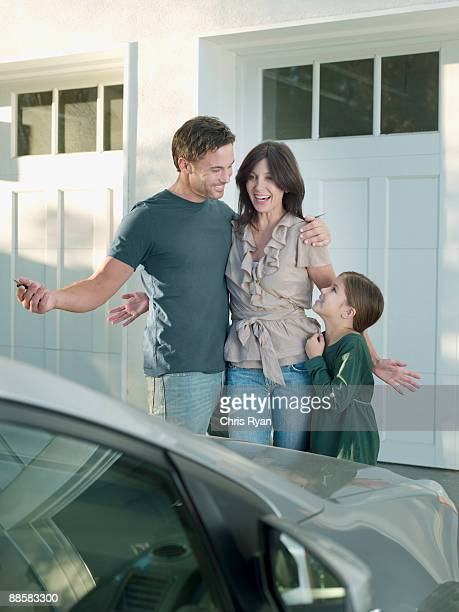Family admiring new car