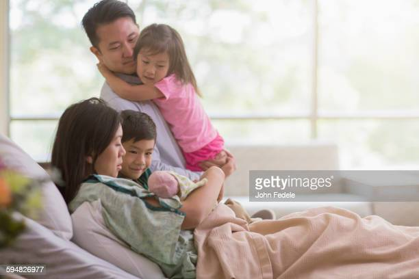 family admiring newborn baby in hospital room - patients brothers stock pictures, royalty-free photos & images