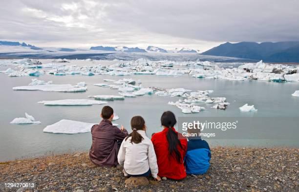 family admiring the view of the mighty vatnajokull glacier - jökulsárlón lagoon stock pictures, royalty-free photos & images