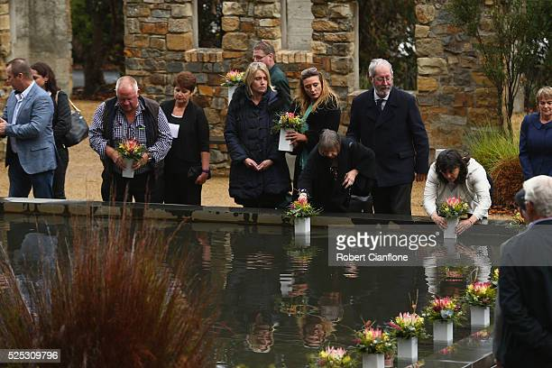 Family and community members lay 35 floral tributes in the Memorial Pool to remeber the victims during the 20th anniversary commemoration service of...