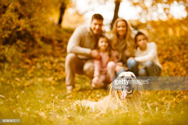 Family and dog in autumn park