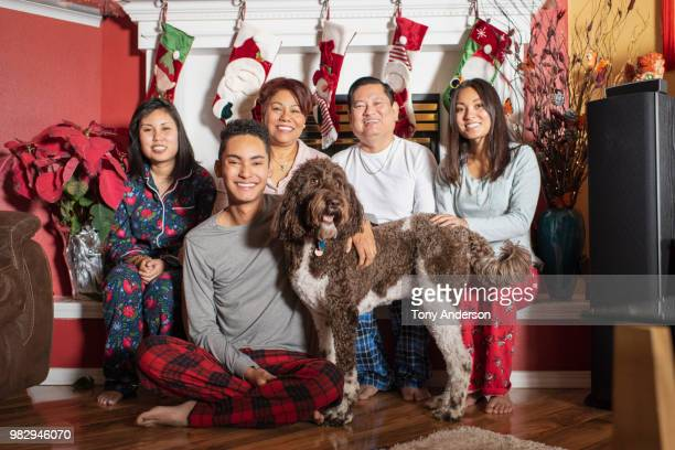 Family and dog sitting together in home decorated for Christmas