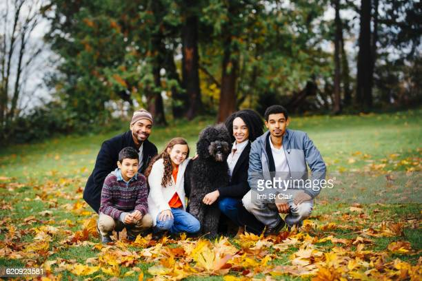 family and dog smiling in park - stepfamily stock photos and pictures