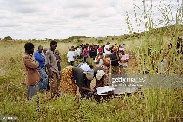 Family and friends attend the funeral of a woman who succumbed to HIV/AIDS in the rural area of Mapepe in Zambia July 2001 The disease is killing...