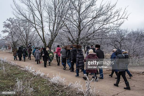 Family and friends carry the casket of Igor Molodetskykh who was killed two days prior when a shell hit his school on February 15 2015 in Artemivsk...