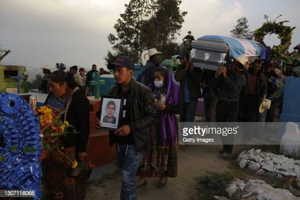 Family and friends carry the coffin of Rivaldo Danilo Jimenez during his burial at the community cemetery on March 14, 2021 in Comitancillo,...