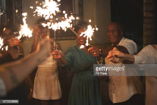 family and friends celebrating new year party with sparkler at home - new year 2020 stock photos and pictures