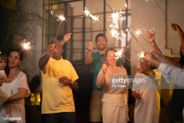 família e amigos em casa a celebrar a festa de ano novo com sparkler - ano novo - fotografias e filmes do acervo