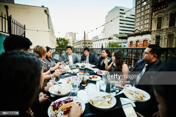 Family and friends dining together on restaurant deck on summer evening