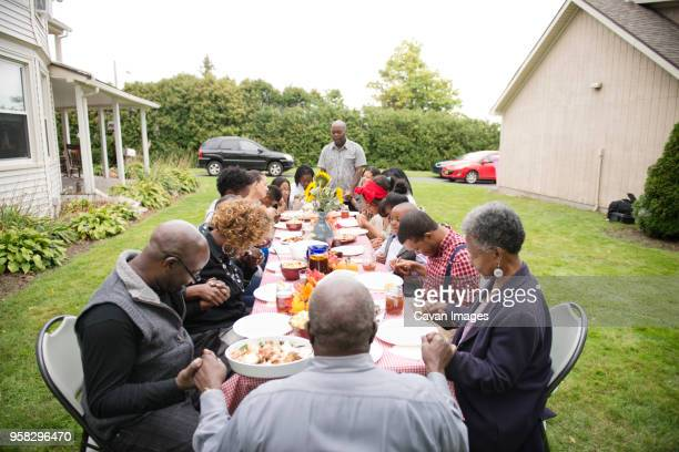 family and friends eating food at picnic table - family reunion stock pictures, royalty-free photos & images
