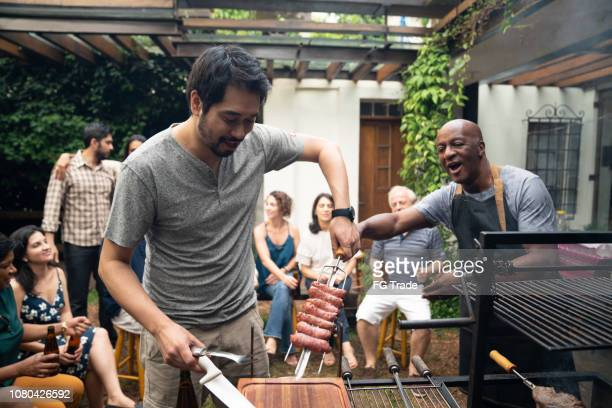 family and friends enjoying a barbecue party at home - guest stock pictures, royalty-free photos & images
