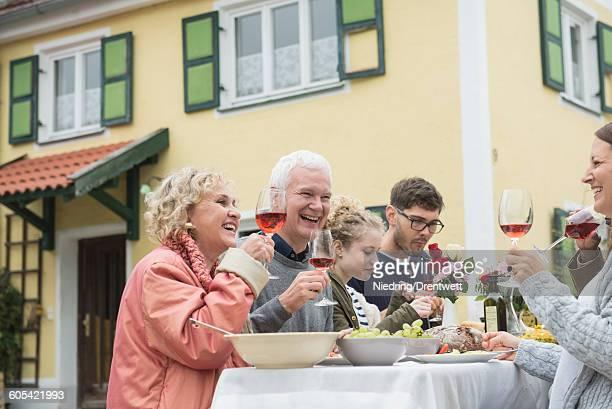 Family and friends enjoying outdoor party at farmhouse, Bavaria, Germany