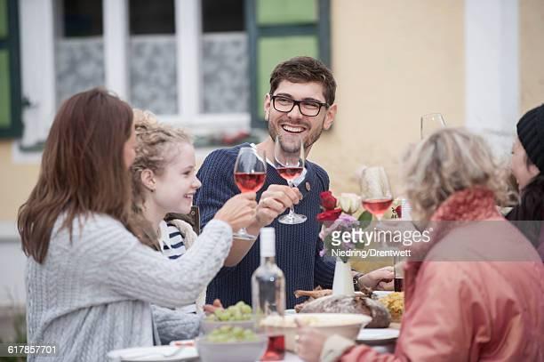 'Family and friends enjoying outdoor party at farmhouse, Bavaria, Germany'