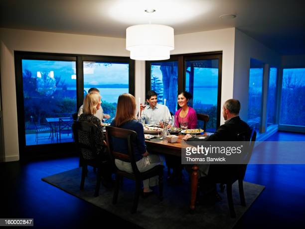 Family and friends in dinning room eating dinner