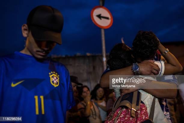 Family and friends make an ecumenical act in honor of those killed in the Raul Brasil School shooting in which two young men shot and killed 8...