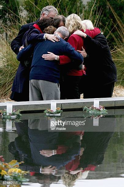Family and friends of those killed in the Port Arthur massacre embrace after laying floating candles in the reflection pool at the memorial site...
