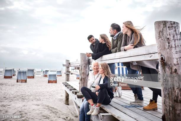 family and friends on boardwalk on the beach - multi generation family stock pictures, royalty-free photos & images