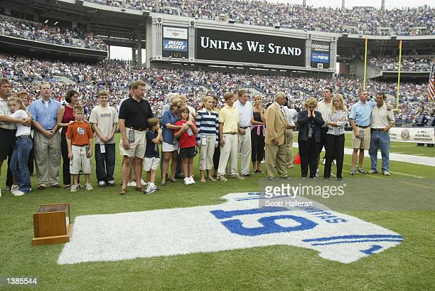 Family and friends pay tribute to Johnny Unitas as they stand behind a jersey painted with his name and uniform number on the grass prior to the game...