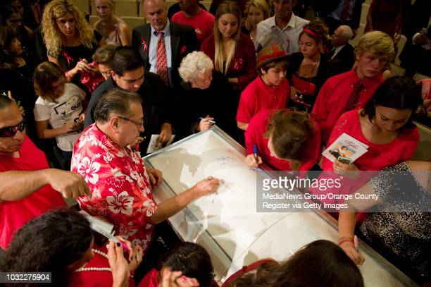 Family and friends sign the casket of Tyler Macleod at the conclusion of a memorial service for the Huntington Beach High School senior who died of a...