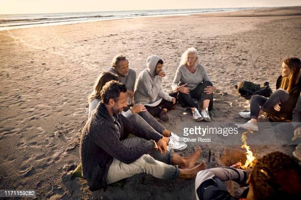 family and friends sitting around campfire on the beach at sunset - キャンプファイヤー ストックフォトと画像