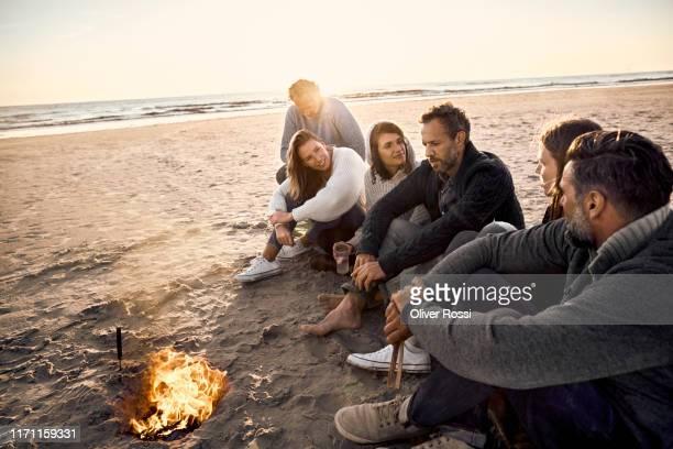 family and friends sitting around campfire on the beach at sunset - mittelgroße personengruppe stock-fotos und bilder