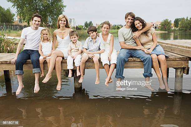 Family and friends sitting on a pier