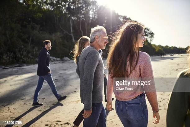 family and friends strolling on the beach - kleine personengruppe stock-fotos und bilder