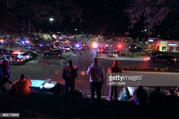 Family and friends wait on a hill to hear word from their loved ones as emergency crews and police on the grounds of the Walmart in Thornton on...