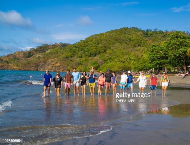 family and friends walking on a beach in costa rica - guanacaste stock pictures, royalty-free photos & images