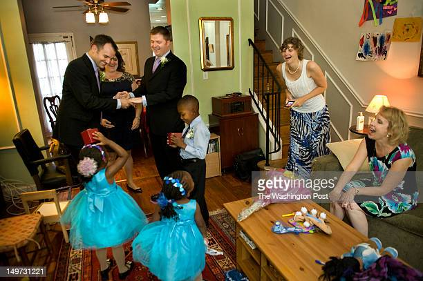 Family and friends watch as Kelly Vielmo and longtime partner Jack Montgomery hold a quick wedding ringbearer rehearsal at home with their adoptive...