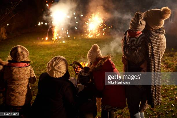 Family and friends watching fireworks in garden