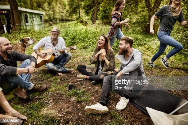 family and friends with guitar around camp fire - einzelnes tier stock-fotos und bilder