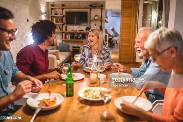 familie en gasten die plezier tijdens een diner - gast stockfoto's en -beelden