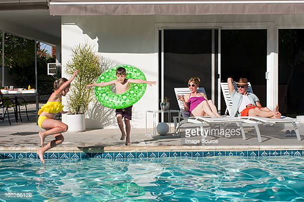 family and outdoor swimming pool - palm springs california stock pictures, royalty-free photos & images