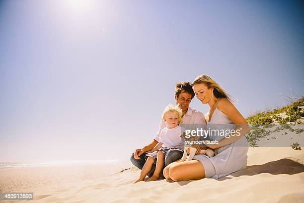 Family and pet dog sitting on beach