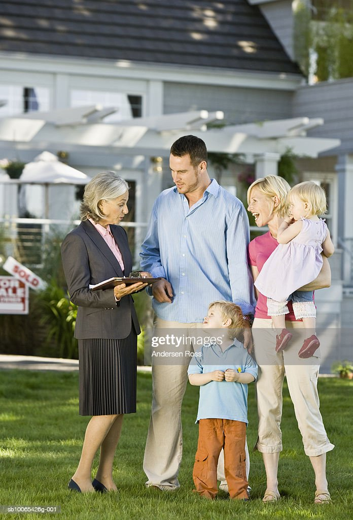 Family and Real Estate Agent in front of Sold House : Foto stock