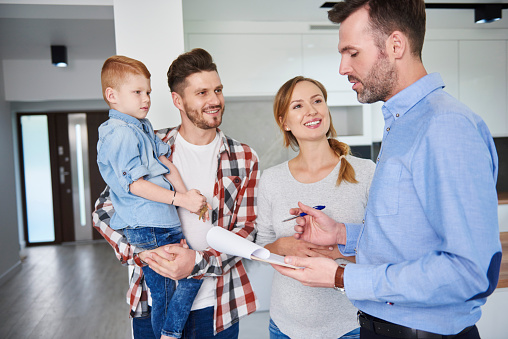 Family and real estate agent talking in new apartment - gettyimageskorea
