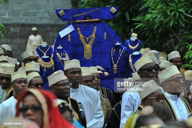 Family and representatives of the grooms family arrive bearing golden jewelry for the bride at a traditional wedding ceremony in Moroni July 28...