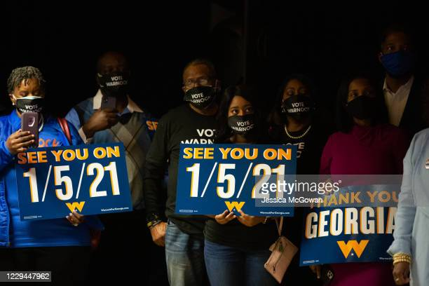 Family and supporters hold runoff signs as Democratic U.S. Senate candidate Rev. Raphael Warnock speaks during an Election Night event on November 3,...