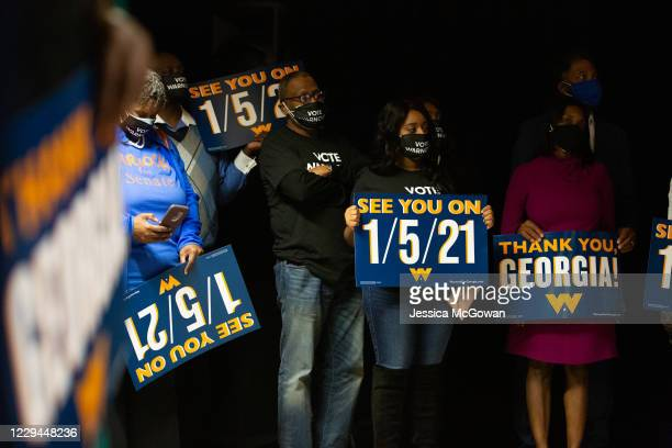 Family and supporters hold runoff signs as Democratic US Senate candidate Rev Raphael Warnock speaks during an Election Night event on November 3...
