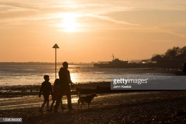 A family and their dog walk together along the beach at sunset on March 26 2020 in Chalkwell England British Prime Minister Boris Johnson announced...
